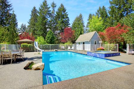 Omheinde achtertuin met terras, zwembad nad jacuzzi Stockfoto
