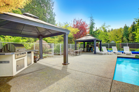 Concrete floor patio area with barbeque, table set, sun chairs and swimming pool photo