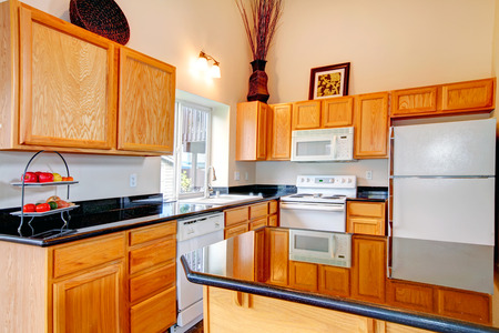 black appliances: Light brown cabinets with black counter tops, white kitchen appliances. Room decorated with dry branches and wicker fruit basket Stock Photo