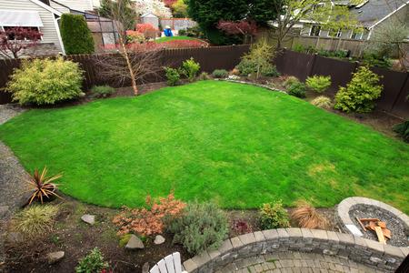 Omheinde groene achtertuin met bomen en bloem bed, stoned patio met een vuurkorf. Uitzicht vanaf staking dek