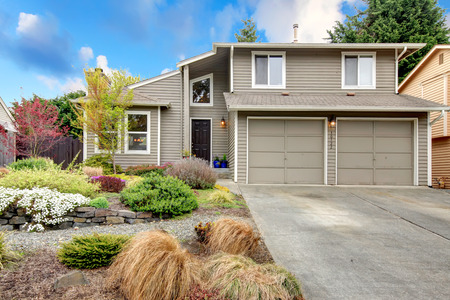 SIding house with garage, drive way and beautiful front flower bed and tree.