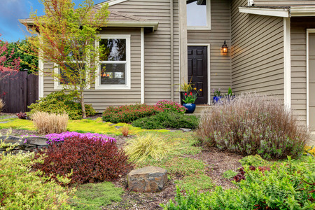 house siding: Siding house entrance with beautiful front flower bed and tree. Stock Photo
