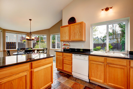 windows: Bright kitchen room with concrete floor, light brown cabinets with black counter tops. Kitchen room open to cozy dining area.