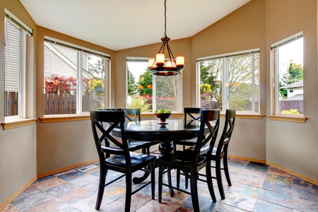 Vaulted ceiling dining rooom with concrete floor and black wooden dining table set photo