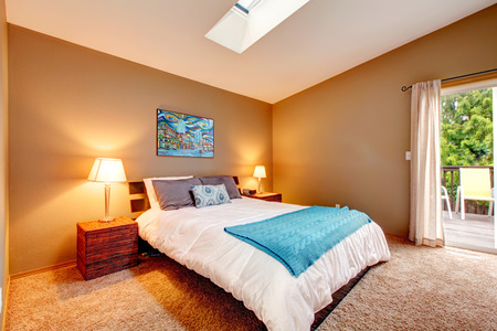 nightstands: Vaulted ceiling bedroom with soft carpet floor and walkout deck. Room furnished with tropical style bed and nightstands. Decorated with wall picture.