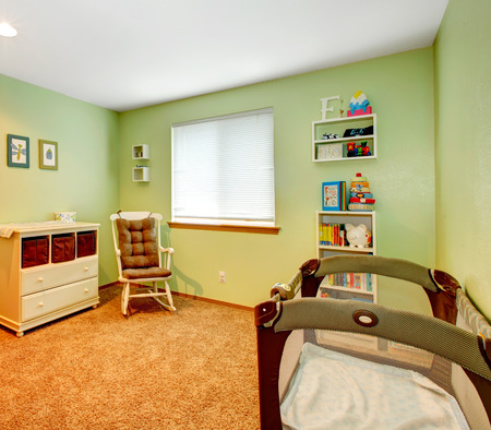 room: Green and beige cozy nursery room with baby crib, rocking chair and wooden cabinet Stock Photo
