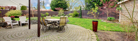 Cozy backyard ared with stoned floor, patio table set and white chairs
