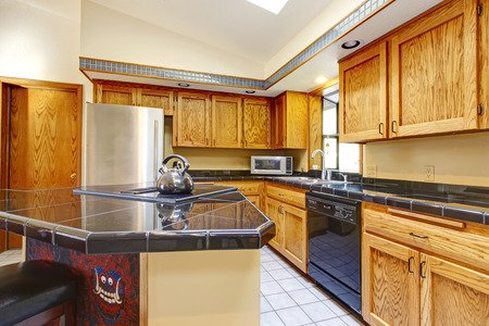 vaulted ceiling: Vaulted ceiling kitchen with light brown storage cabinets, black counter tops, tile floor, steel appliances.