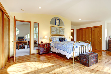 nightstand: Big bright bedroom with hardwood floor, antique bed, chest and nightstand. Stock Photo