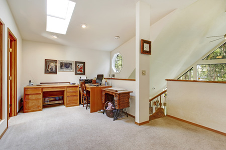 Bright vaulted ceiling upstairs office room with carpet floor, wooden desk and cabinets, antique sewing machine Banco de Imagens