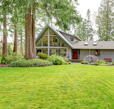 Tile roof countryside house with glass wall, porch and garage. Green lawn together with fir trees and flower bed make curb appeal stand out. photo