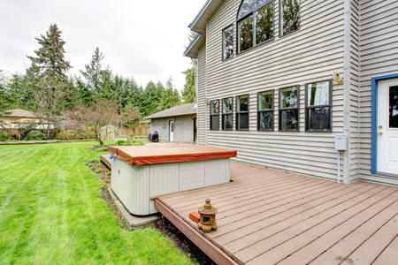 house siding: Siding house with walkout back deck overlooking green lawn and garden bed Stock Photo