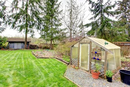 Platteland achtertuin met tuin bed, groene huis en houten schuur