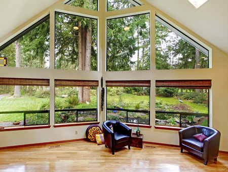 big windows: Bright living room with vaulted high ceiling, hardwood floor and glass wall  Furnished with black leather chairs and piano