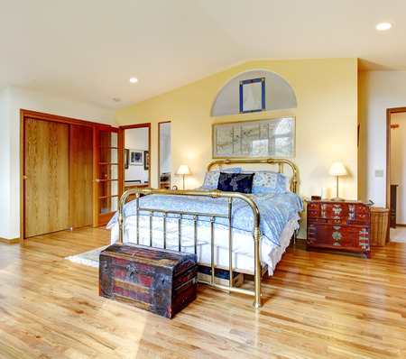 nightstand: Big bright bedroom with hardwood floor, antique bed, chest and nightstand