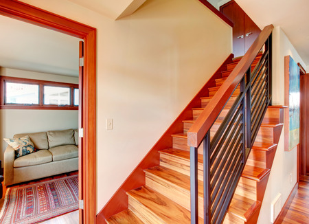 hardwood: Ivory hallway with hardwood floor and stairs. Stairs with iron railings