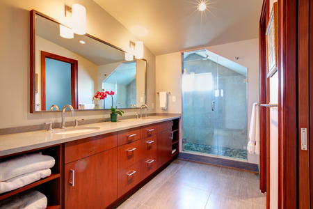 vaulted: Bright bathroom with bright brown cabinets,  mirror, glass door shower with vaulted ceiling.