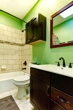 Elegant bathroom with green wall, tile decorated wall, dark brown bashbasin cabinet with white counter top photo