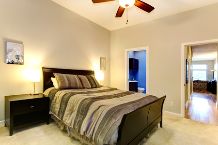 Soft tones master bedroom with carpet floor, dark brown bed and nightstands. photo