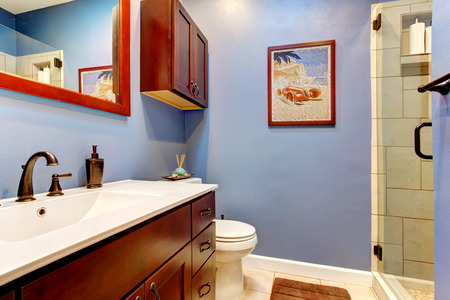 washbasin: Contrast color bathroom with lavender wall and cherry color washbasin cabinet with white counter top Stock Photo