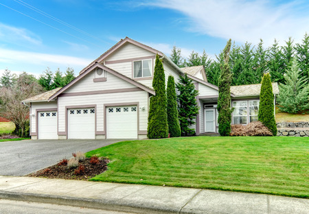 curb appeal: Two story clapboard siding house with garage, drive way, green lawn and fir trees