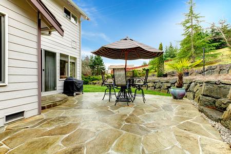 Betonnen vloer gezellige terras met ijzeren tafel set en een patio paraplu. Patio omgeven door groene terras landscaping Stockfoto