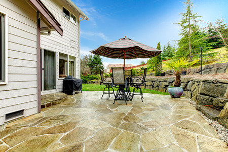 and the area: Concrete floor cozy patio area with iron table set and patio umbrella. Patio area surrounded by green terrace landscaping Stock Photo