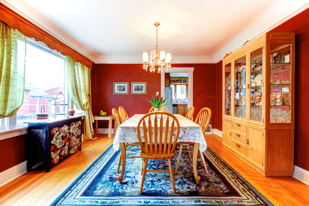 Red dining room with hardwood floor and rug. Furnishes with rustic wooden table, old style glass door cabinet and black storage cabinet