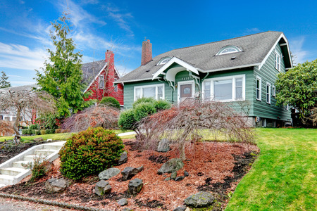 house siding: Green clapboard house with tile roof. Beautiful landscaping idea