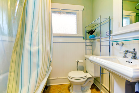 Bright bathroom with window. Green and white  wall matches with striped green curtains. photo