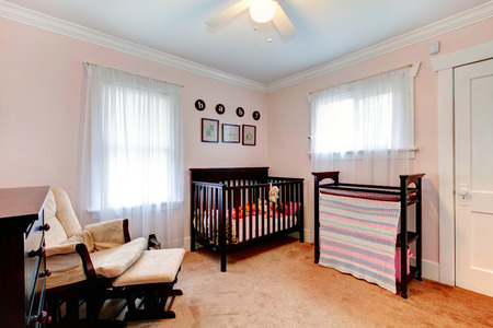 Bright nursery room with light pink walls, carpet floor  Furnished with dark brown wooden crib, chair and dresser photo