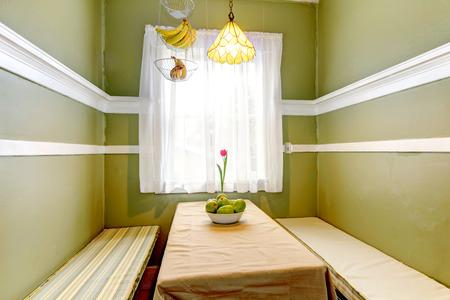 canastas con frutas: Peque�o comedor verde con mesa y bancos, colgando cestas de fruta.