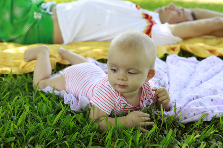 six months: Six months cute blue eyes baby laying on the blanket. Father is laying behind her. Stock Photo