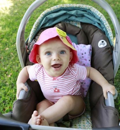 six months: Blue eyes pretty six months baby girl smiling in her stroller