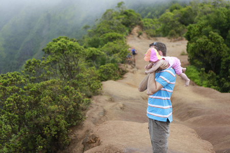 memorable: Memorable moments in familys life. Father is holding his lovely baby on shoulder  and enjoying amazing view of Kauai landscape.