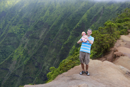 memorable: Memorable moments in familys life. Father is holding his lovely baby in Kauai, Hawaiian islands