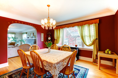 Red dining room with hardwood floor and rug. Furnishes with rustic wooden table, old style glass door cabinet and black storage cabinet photo