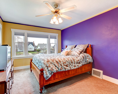 Bright bedroom with purple and yellow walls, carpet floor. Furnished with carved wood bed, cabinet and tv photo