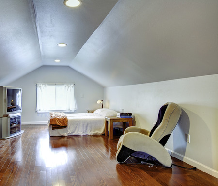nightstand: Light blue low and vaulted ceiling bedroom with hardwood floor. Room furnished with bed, tv, nightstand and massage chair