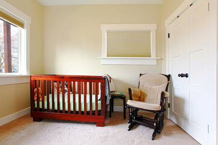 Nursery with simple setting and beige walls. Stock Photo - 26094571