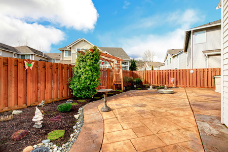 lawn area: Fenced backyard with concrete tile floor deck and decorated flower bed