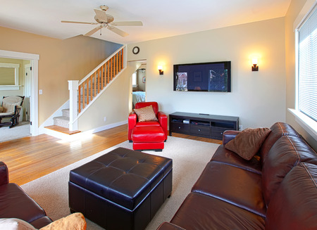 designer chair: Living room with red leather chair, staircase and television