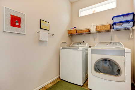 Bright laundry room with washer and dryer. Wall shelf with wicker baskets photo