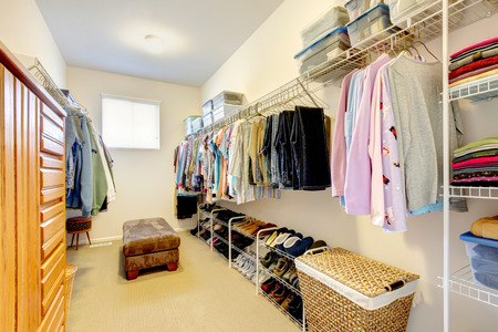 Big walk-in closet with shelves for clothes and shoes, dresser and wicker baskets Stock Photo