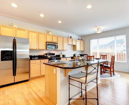 Large kitchen room with hardwood floor. Light tones storage cabinets with black counter tops photo