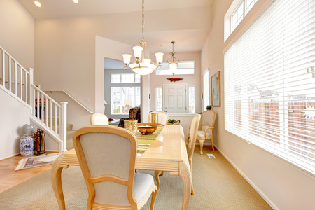 High ceiling dining room with light wooden table  and chairs. View of stairs Stock Photo - 26094553