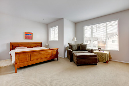 Large bright bedroom with carved wood bed, chair and table. photo