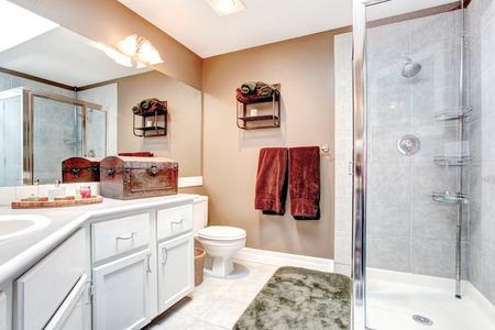 etagere murale: Beige et salle de bains avec douche blanche de porte en verre, carrelage et tapis vert tendre. D�cor� avec une serviette de Bourgogne, coffre ancien et �tag�re murale