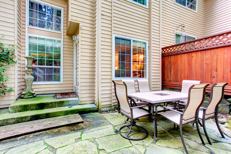 house siding: Concrete tile floor backyard with patio table set.