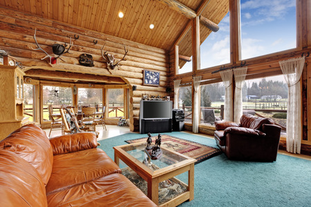 Large beautiful living room in log cabin house with leather chair and couch. View of rustic dining area from living room Archivio Fotografico